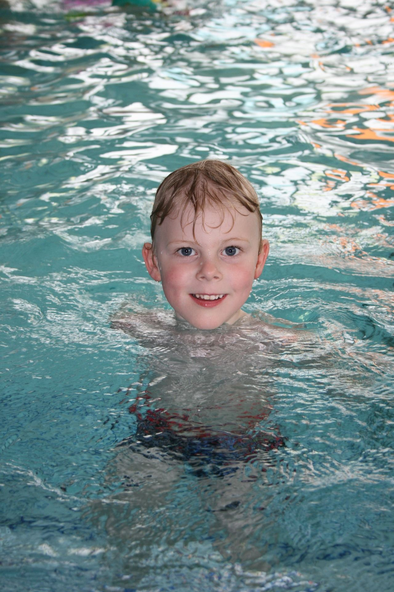 little boy treading water in pool